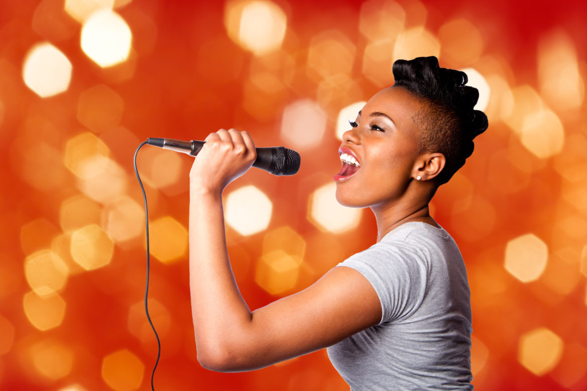 Beautiful teenager woman singing kareoke concert artist holding microphone, on red orange blurred lights background.